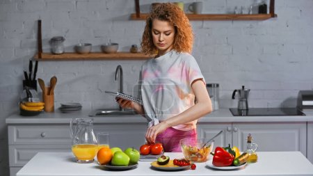 curly woman holding holding notebook and weighing tomatoes near vegetables and orange juice on table