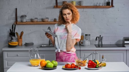 pensive woman holding notebook near vegetables and fruits on kitchen table