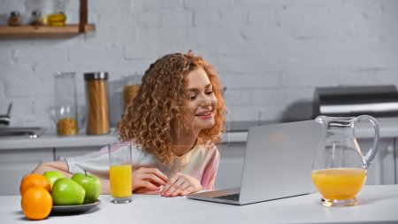 Photo for Cheerful woman watching movie on laptop near fruits on kitchen table - Royalty Free Image