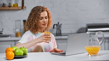 Photo for Curly young woman looking at laptop while holding glass of orange juice near fruits on kitchen table - Royalty Free Image