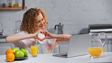 Photo for Curly young woman looking at laptop while showing heart sign with hands during video call - Royalty Free Image