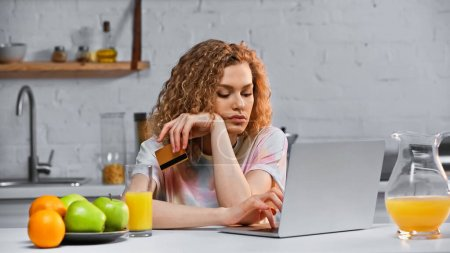 Photo for Curly young woman holding credit card while shopping online in kitchen - Royalty Free Image