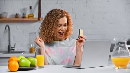 Photo for Excited young woman holding credit card while shopping online in kitchen - Royalty Free Image