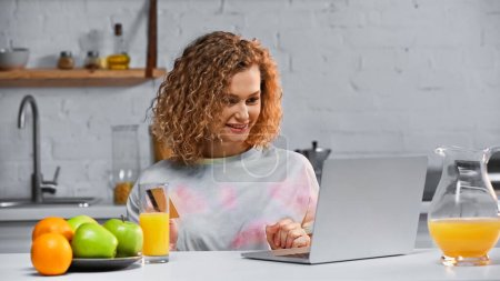 Photo for Happy young woman holding credit card while shopping online in kitchen - Royalty Free Image