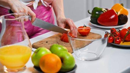 Ausgeschnittene Ansicht einer Frau, die Tomaten auf Schneidebrett schneidet