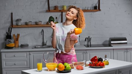 Photo for Curly young woman holding bell peppers near fresh veggies in kitchen - Royalty Free Image
