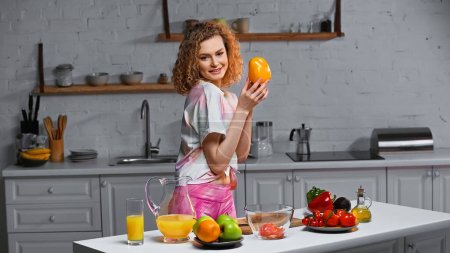 Photo for Happy young woman holding bell pepper near fresh veggies in kitchen - Royalty Free Image
