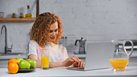 Photo for Joyful woman looking at laptop near fruits and glass of orange juice on table - Royalty Free Image