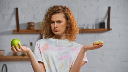 curly young woman choosing between apple  and donut