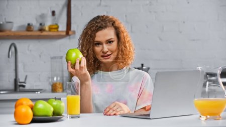 Photo for Curly woman holding apple while looking at camera near laptop and fruits on table - Royalty Free Image