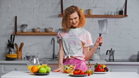cheerful woman holding huge knife near fresh salad in bowl and fruits on table