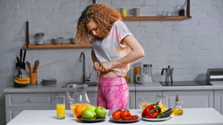 Photo for Curly woman measuring waist with measuring tape near veggies on kitchen table - Royalty Free Image