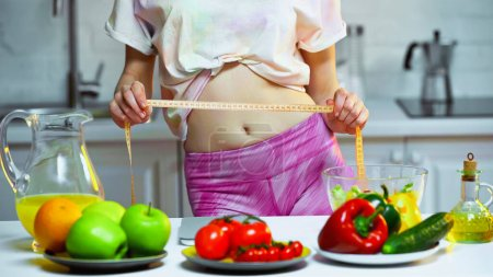partial view of woman measuring waist near vegetables and fruits on blurred foreground
