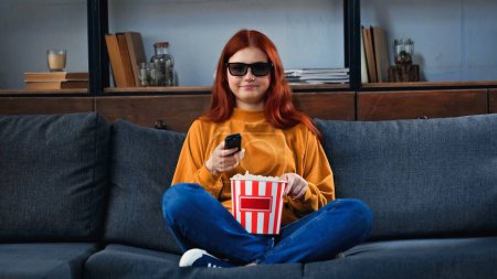 Smiling girl in 3d glasses holding popcorn and remote controller at home