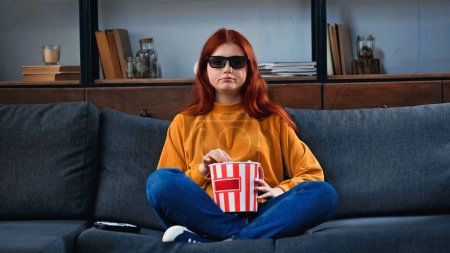 Teenager in 3d glasses holding bucket with popcorn near remote controller on couch