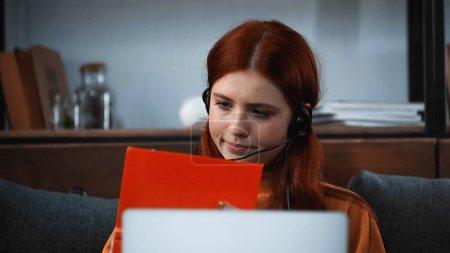 Photo pour Étudiant en casque regardant le livre près de l'ordinateur portable sur le premier plan flou à la maison - image libre de droit