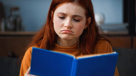 Sad girl reading book on blurred foreground