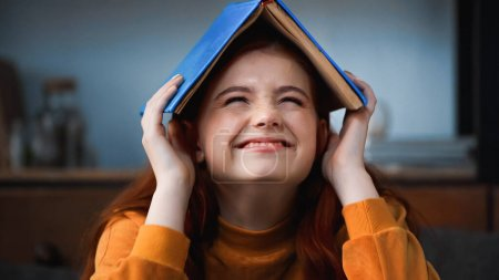 Photo for Happy teenager holding book above head at home - Royalty Free Image