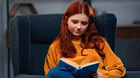 Teenager reading book on blurred foreground in armchair