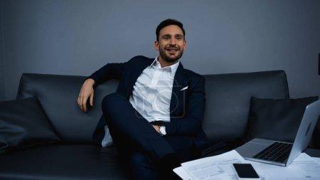 Photo pour Homme d'affaires souriant regardant loin près des gadgets et des papiers sur le premier plan flou à l'hôtel - image libre de droit