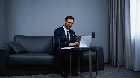 Smiling businessman typing on laptop near documents on table in hotel room