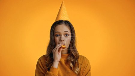 teenage girl in party cap blowing party horn isolated on yellow