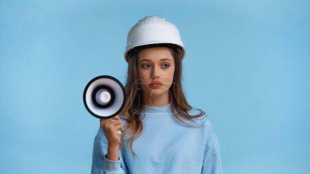 Teenagermädchen mit Hut hält Megafon isoliert auf blauem Grund