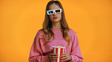 teenage girl in 3d glasses holding bucket with popcorn isolated on yellow