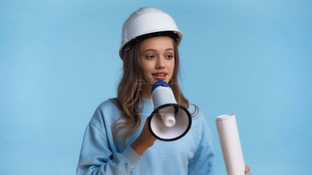 Photo pour Adolescent fille dans Dur chapeau tenant mégaphone et roulé plan isolé sur bleu - image libre de droit