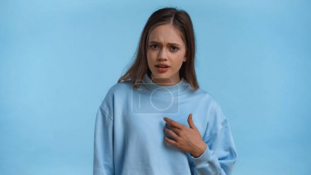 Photo pour Insatisfait adolescent fille en sweat-shirt pointant vers elle-même isolé sur bleu - image libre de droit