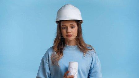 Photo pour Adolescent fille dans Dur chapeau tenant roulé plan isolé sur bleu - image libre de droit