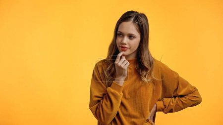 Photo for Teenager in sweater looking away while standing with hand on hip isolated on yellow - Royalty Free Image