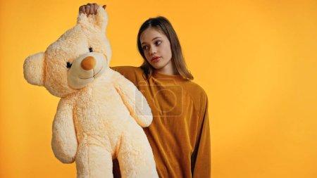 adolescente disgustado en suéter mirando osito de peluche aislado en amarillo