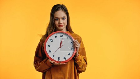 smiling teenage girl in sweater holding clock isolated on yellow