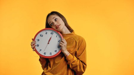 smiling teenager in sweater holding clock isolated on yellow