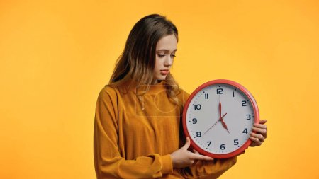 teenage girl in sweater looking at clock isolated on yellow