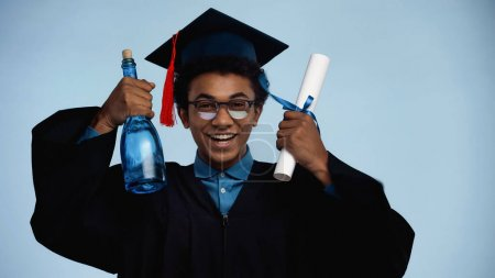 african american teenage boy in graduation gown and cap holding diploma and bottle with champagne isolated on blue