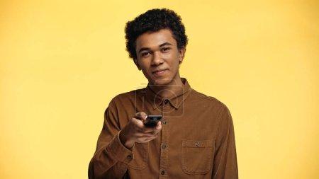 fröhliche afrikanisch-amerikanische Teenager mit Fernbedienung isoliert auf gelb