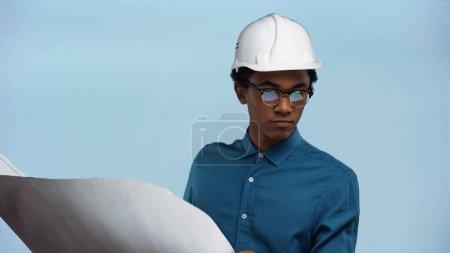 Photo pour Afro-américain adolescent garçon en casque de sécurité tenant plan isolé sur bleu - image libre de droit