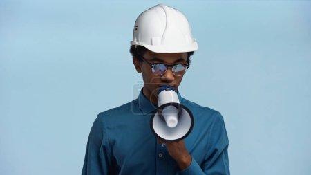 afrikanisch-amerikanischer Teenager mit Hut hält Megafon in der Hand, während er isoliert auf blau spricht