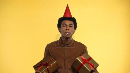 african american teenager in party cap blowing horn while holding presents isolated on yellow