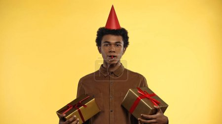 afrikanisch-amerikanischer Teenager in Partymütze mit Geschenkschachteln isoliert auf gelb