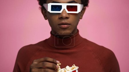 african american teenager in 3d glasses holding popcorn isolated on pink