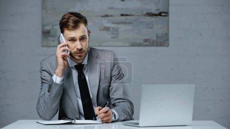 Geschäftsmann im Anzug spricht auf Smartphone und hält Stift neben Notizbuch auf Schreibtisch