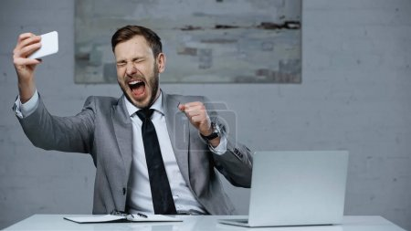 Photo for Excited businessman with open mouth taking selfie on smartphone near laptop on desk - Royalty Free Image