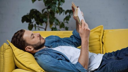 Photo for Bearded man lying on sofa and reading book in living room - Royalty Free Image