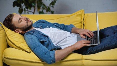tired freelancer sleeping on sofa with laptop