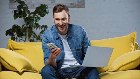 homme heureux tenant des dollars près d'un ordinateur portable tout en étant assis sur le canapé