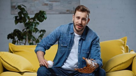 Photo for Bearded man in leather baseball glove holding ball in living room - Royalty Free Image
