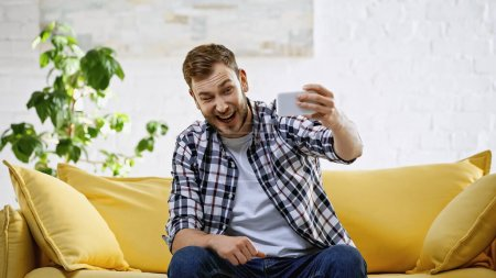 Photo pour Excité homme prendre selfie sur téléphone mobile tout en clignant des yeux dans le salon - image libre de droit